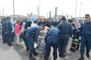 うるま市の女性遺体遺棄事件を受け、座り込み行動をする市民らを排除する機動隊員=21日、名護市辺野古キャンプ・シュワブゲート前