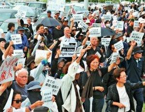 キャンプ瑞慶覧に向かってプラカードを掲げ、無言で抗議する集会参加者=22日午後2時51分、北中城村・石平ゲート前