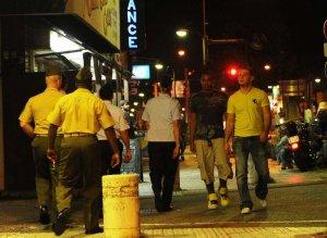 制服姿の米兵に促され、基地内に帰る若い米兵ら=2012年10月20日 沖縄市の空港通り