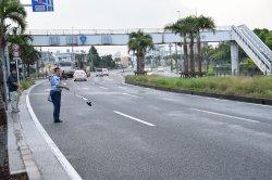 二等兵曹が逆走した事故現場を調べる警察官=5日午前6時40分ごろ、嘉手納町水釜の国道58号