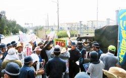 米軍キャンプ・シュワブから出る米軍車両を止めようと、抗議の声を上げる市民ら=6日午前、名護市辺野古