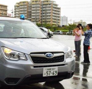 地域巡回に出発する青色回転灯のパトロール車=15日午後、那覇市おもろまちの沖縄総合事務局駐車場