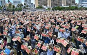 「海兵隊は撤退を」のメッセージボードを一斉に掲げる参加者=19日午後、那覇市・奥武山運動公園陸上競技場
