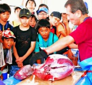 マグロの解体で歓声を上げる子どもたち=16日、久米島漁協セリ市場