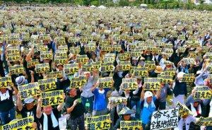 「怒りは限界を超えた」のメッセージボードを一斉に掲げる県民大会の参加者=19日午後、那覇市・奥武山公園陸上競技場