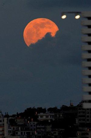 ストロベリームーンといわれる赤みがかった月が雲の切れ間から顔をのぞかせた=20日午後7時20分、那覇市久茂地から望む(喜屋武綾菜撮影)