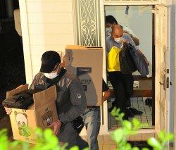 被告宅の家宅捜査を終え、証拠の入ったダンボール箱を運び出す捜査員ら=5月