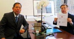 米事務所の開設許可証を掲げる翁長雄志知事(右)と駐在員の平安山英雄氏=2015年5月、米ワシントン