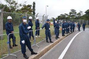 米軍北部訓練場メインゲート前に設置された鉄柵。動かされないよう警備にあたる機動隊=11日午後4時52分、東村高江