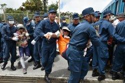 北部訓練場への資材搬入に抗議し座り込む住民を排除する沖縄県警機動隊員=12日午前、東村高江