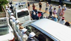 市民が止めた車列の間に立つ防衛局職員(左側)=16日、東村高江・N1地区ゲート(記事中の職員とは関係ありません)