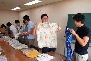 かりゆしウエアの展示販売会で品定めをする職員=6月24日、愛知県・蒲郡市役所(同市提供)