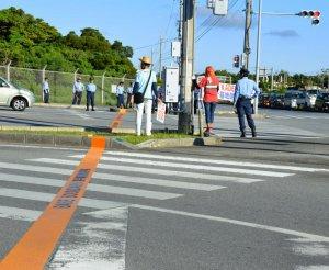 米軍嘉手納基地第3ゲート前の横断歩道を斜めに区切るように引かれた「嘉手納基地境界線」=22日、沖縄市白川