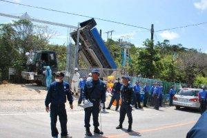 N1地区出入り口内に砂利を運び入れるトラック=25日午前11時14分、東村高江