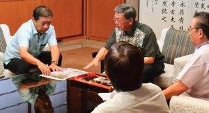 資料を示し、翁長雄志知事に説明する桑江朝千夫沖縄市長(左)=8日、県庁