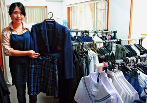 県内各校の制服がずらりと並ぶ店内。與那城さんは「不要な学生服をぜひ売ってもらいたい」と話す=23日、浦添市沢岻
