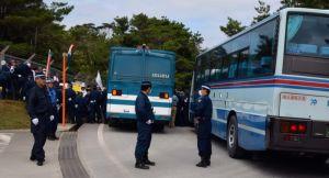 ゲート(手前左側)への搬入を阻止しようと抗議する市民らを、隊員の人垣と機動隊車両(左)でふさぎ、さらに県道上に貸し切りバスを留め置いて通行を規制した=26日正午ごろ、東村高江・米軍北部訓練場メインゲート前