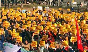 「沖縄に基地NO!」の黄色いプラカードを掲げる参加者=日、大阪市・扇町公園