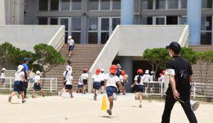 監視員(右)の指示で、「半地下」と呼ばれる場所へ避難する児童ら=7日午前11時27分、宜野湾市新城・普天間第二小学校
