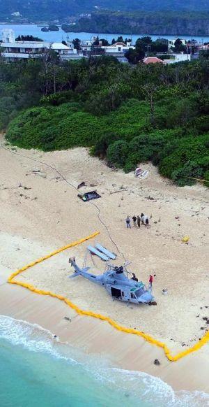ローターが全て取り外された米軍UH1ヘリ(手前)。不時着現場から約50メートルの距離に住宅地がある=7日午前11時すぎ、うるま市・伊計島(小型無人機から)