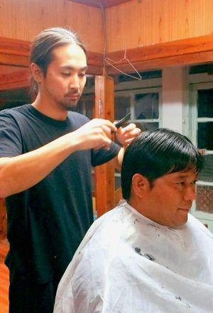 「島の美よう室」を継いだ神保了さん。子どもからお年寄りまで、幅広い世代の髪を切る=6日、渡名喜村(笹口真利衣通信員撮影)