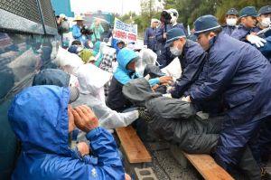 工事用ゲート前に座り込んだ市民らを強制排除する県警機動隊=18日午前9時ごろ、名護市辺野古の米軍キャンプ・シュワブ前
