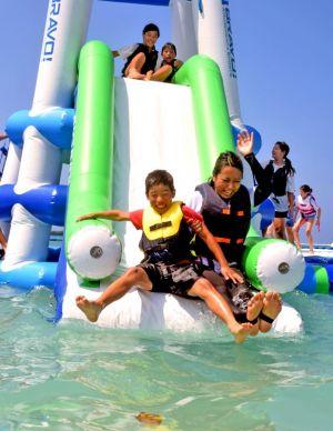海上に設置された滑り台を楽しむ行楽客=17日、恩納村