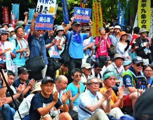 謝花喜一郎副知事のあいさつを音声中継で聞き、拍手を送る東京の集会参加者=11日、東京都豊島区の東池袋中央公園