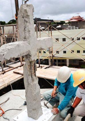 旧会堂の屋上に設置された十字架。沖縄での銃撃戦で傷ついた様子が写真や証言から再現された=21日、那覇市・首里教会