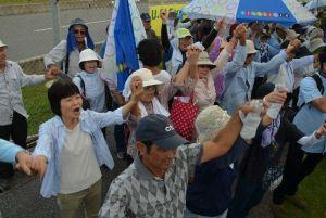 辺野古新基地建設に対し、手をつないで反対の声を上げる集会参加者=7日午後0時40分、名護市辺野古