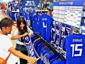 サッカー日本代表の応援グッズを品定めするサポーター=25日、豊見城市のスポーツデポ豊崎店