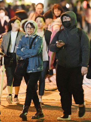 厚着姿で交差点を歩く人たち=9日午後6時半ごろ、那覇市久茂地(田嶋正雄撮影)