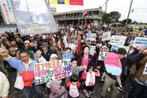米軍機からの落下事故に抗議し、こぶしを突き上げる大会参加者=29日午後2時58分、宜野湾市役所前