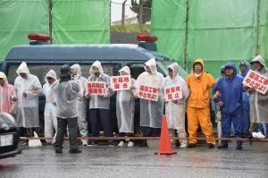 雨の中、工事車両の進入を防ぐため工事車両用ゲート前でスクラムを組む市民ら=30日午前8時40分