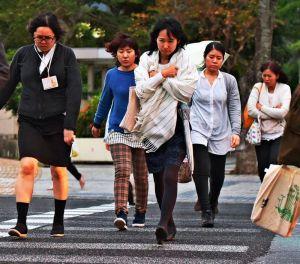 北風が吹く中、足早に横断歩道を渡る人たち=27日午後5時すぎ、那覇市久茂地(渡辺奈々撮影)