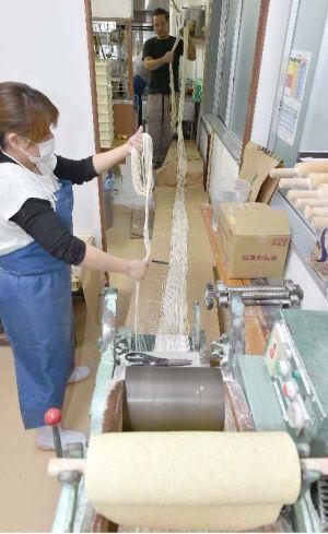 1本5メートルに切った麺をまとめる三竹寿製麺所の職員=30日、浦添市経塚