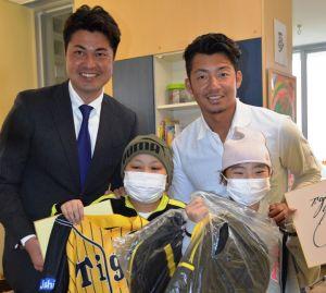 子どもたちを激励する鳥谷敬選手(後列右)と比嘉寿光さん(同左)=5日、南風原町の県立南部医療センター・こども医療センター