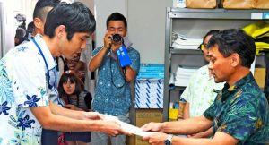 米軍キャンプ・シュワブ沖の岩礁破砕許可申請手続きについての回答書を県水産課(右)に提出する沖縄防衛局の職員=1日、県庁
