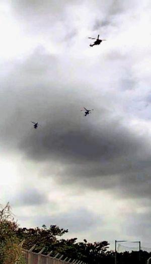 防衛省が公開した、宜野湾市の市立普天間第二小の上空を飛行する米軍ヘリコプターの画像=18日午後