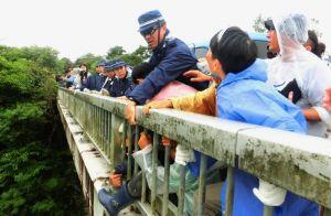 高江橋の欄干にしがみつく住民を排除する機動隊=7日、東村高江