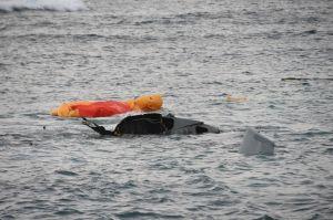 バラバラになって墜落現場の海上を漂うオスプレイの部品や救命ボート=14日午前7時すぎ、名護市安部