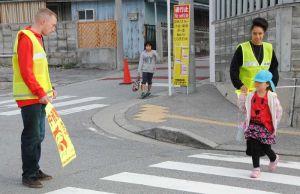 子どもたちの登校を見守り、交通安全のボランティアをする米兵有志=北谷町吉原・北玉小学校前