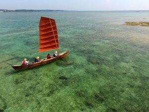 エメラルドグリーン色の海を風を受け進む帆かけサバニ(小型無人機から)
