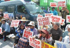新基地建設に伴う護岸着工に抗議し、プラカードを掲げて座り込む市民=25日午前10時すぎ、名護市辺野古