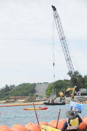 名護市辺野古の米軍キャンプ・シュワブ沿岸では、新基地建設に反対する市民がカヌー16艇で抗議する中、護岸の石積み作業が行われた=26日午前9時20分ごろ
