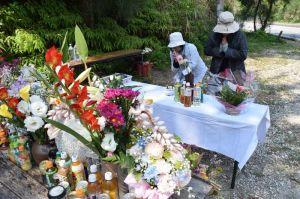 被害女性を悼む献花台に手を合わせる女性たち。多くの花が供えられていた=28日、恩納村安富祖