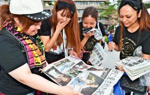 配布された号外に見入る安室奈美恵さんのファン=23日午後6時52分、那覇市久茂地(金城健太撮影)