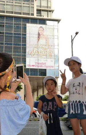 安室奈美恵さんの巨大ポスターをバックに記念撮影する人たち=9日、那覇市久茂地・タイムスビルイムスビル(古謝克公撮影)