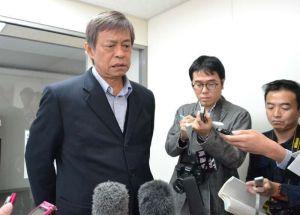 記者団の取材に厳しい表情で答える謝花喜一郎知事公室長=21日午後0時38分、沖縄県庁
