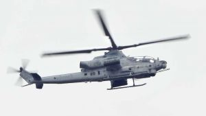 普天間飛行場から再び飛行し名護市上空を飛ぶ、読谷村に8日不時着したAH1攻撃ヘリ=9日午後3時55分